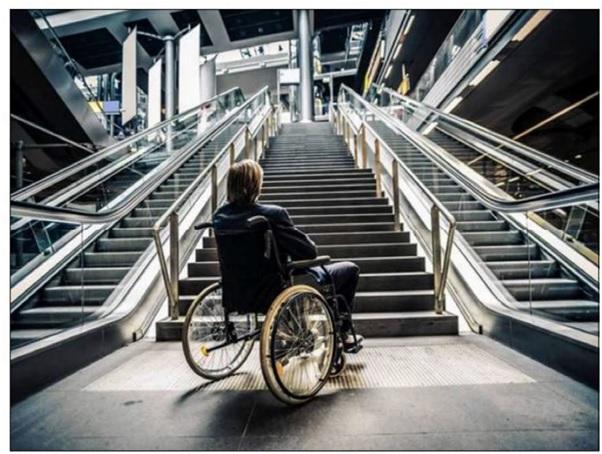 Osoba na wózku patrzy z dołu na wysokie schody, w tym dwa ciągi schodów ruchomych.