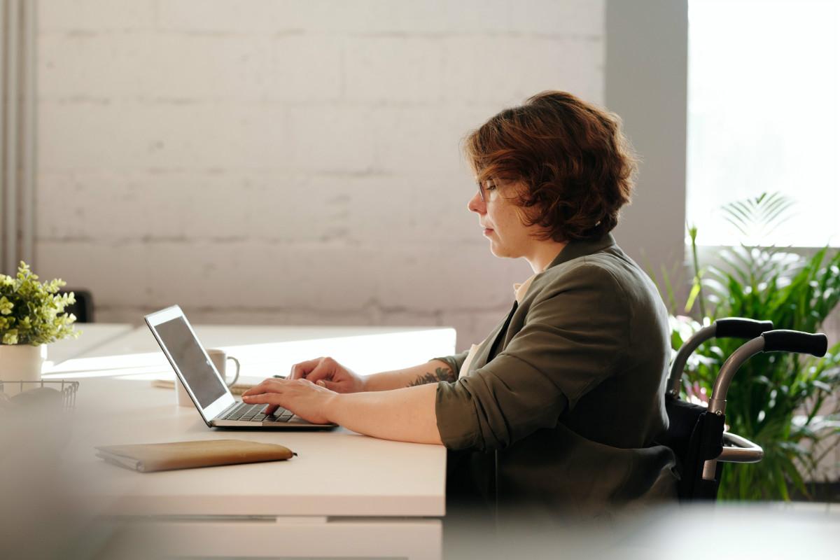 Osoba niepełnosprawna siedząca przy biurku i pracująca na laptopie